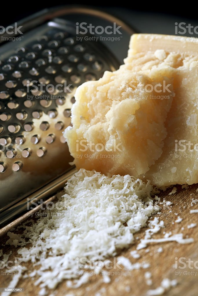 Block of freshly grated Parmesan cheese with cheese grater stock photo