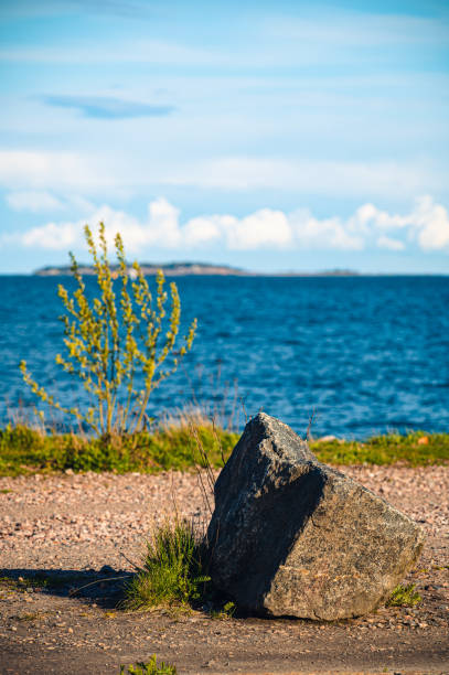 A block of granite standing next to waterfront. stock photo