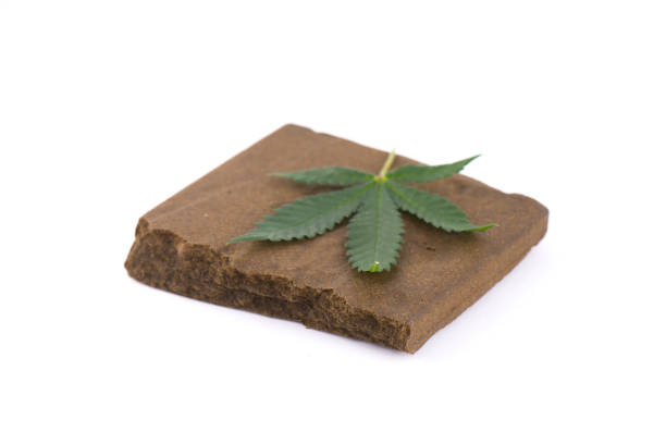Block of hashish, a medical marijuana concentrate isolated with cannabis leaf stock photo