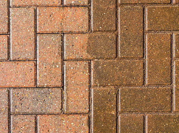 block paving half jet washed and half still dirty - high pressure cleaning stock photos and pictures