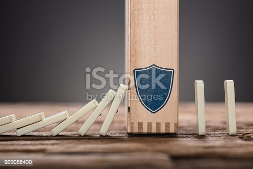 istock Block With Shield Symbol Amidst Falling Domino Pieces 922088400