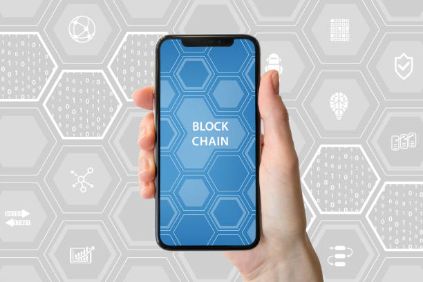 Blockchain and cryptocurrency concept. Hand holding modern bezel-free smartphone in front of neutral background. stock photo
