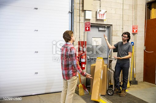 A blocked fire exit door in an industrial building such as a warehouse or factory.  Blocked fire exits are very dangerous and they are in violation of safety regulations. A supervisor is explaining the dangers of blocking an emergency exit to a new employee.