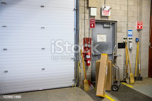 A blocked fire exit door in an industrial building such as a warehouse or factory.  Blocked fire exits are very dangerous and they are in violation of safety regulations.