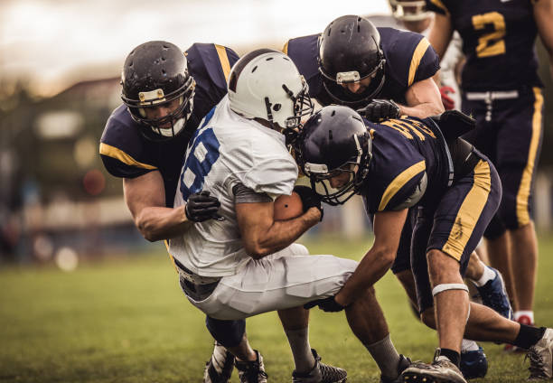 Blocking an offensive player! American football players tackling opposite's team quarterback during the match. american football player stock pictures, royalty-free photos & images