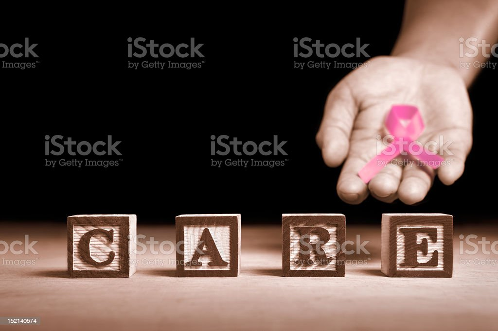 Blocks spelling out care with a hand holding a pink ribbon royalty-free stock photo