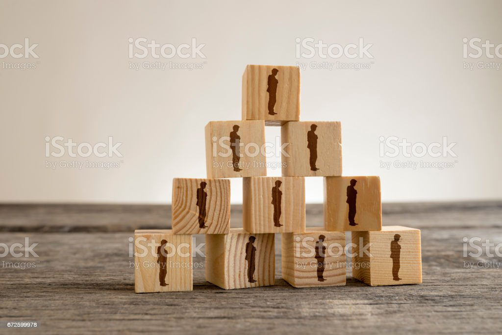 Blocks with businessman silhouettes structured into a pyramid stock photo