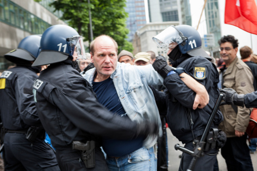 Frankfurt, Germany - June 1, 2013: A male protestor is trying to break through the riot police cordon - and getting into a fight at Blockupy 2013 demonstration in the city center of Frankfurt. Blockupy is a left-wing political network of several organizations. The name derives from its plan for a \