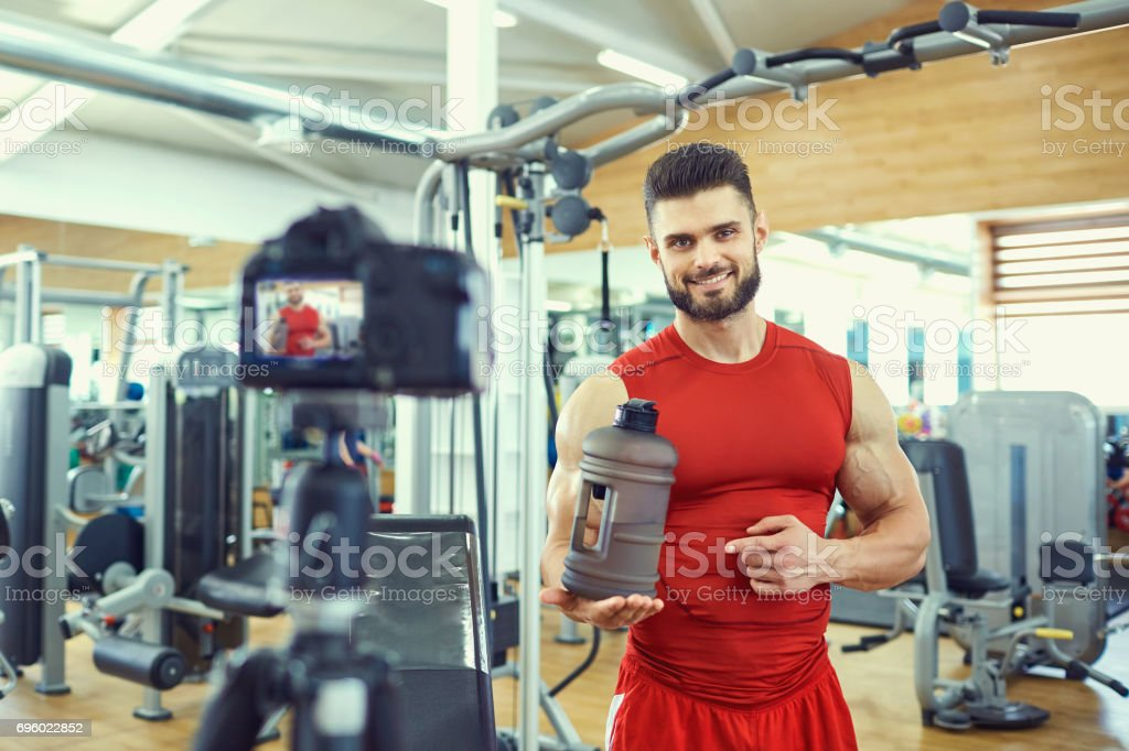 Blogger athlete makes a video about healthy eating in the gym stock photo