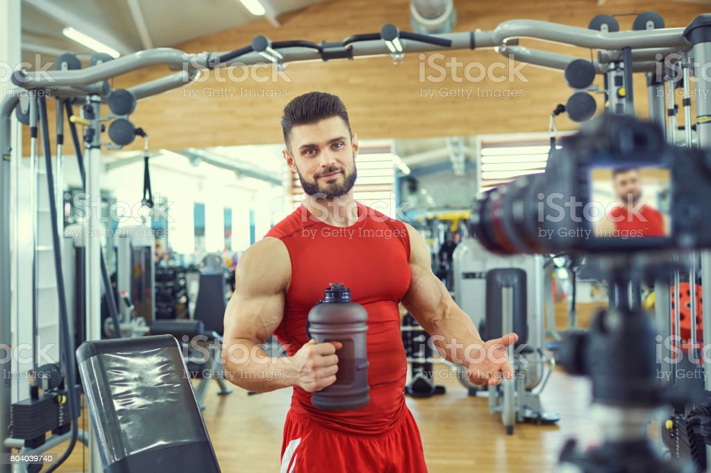 Blogger athlete makes a video in the gym. stock photo