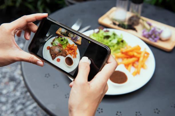 Blogger-Hände mit Smartphone fotografieren Kotelett Steak mit Salat und Pommes frites auf weißen Teller im Garten. Ansicht von oben. – Foto