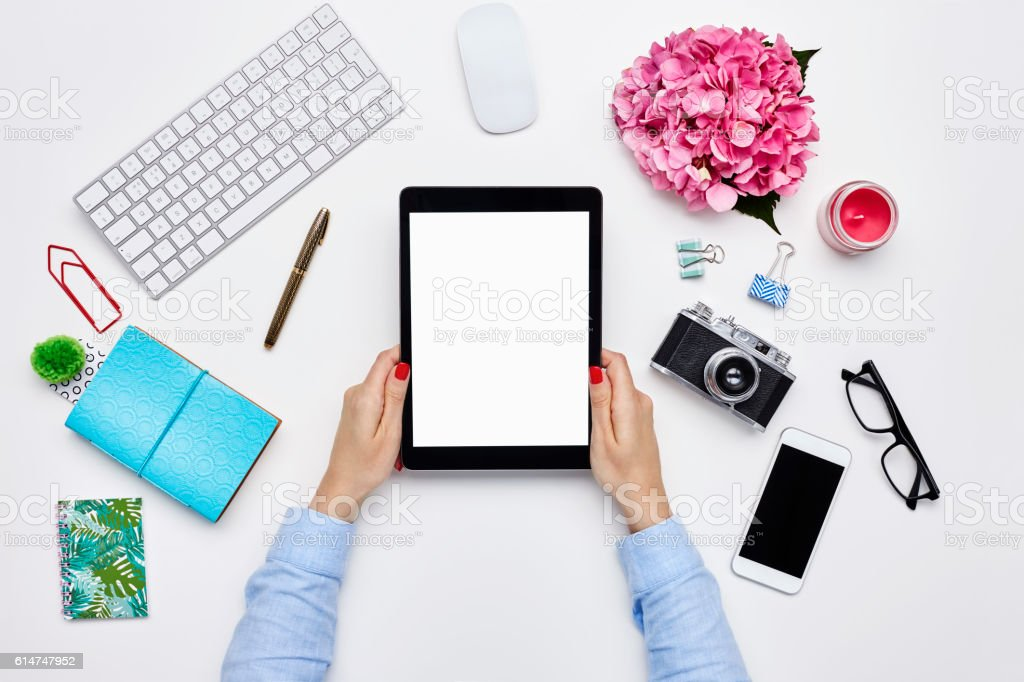 Blogger holding digital tablet by desk supplies on white background