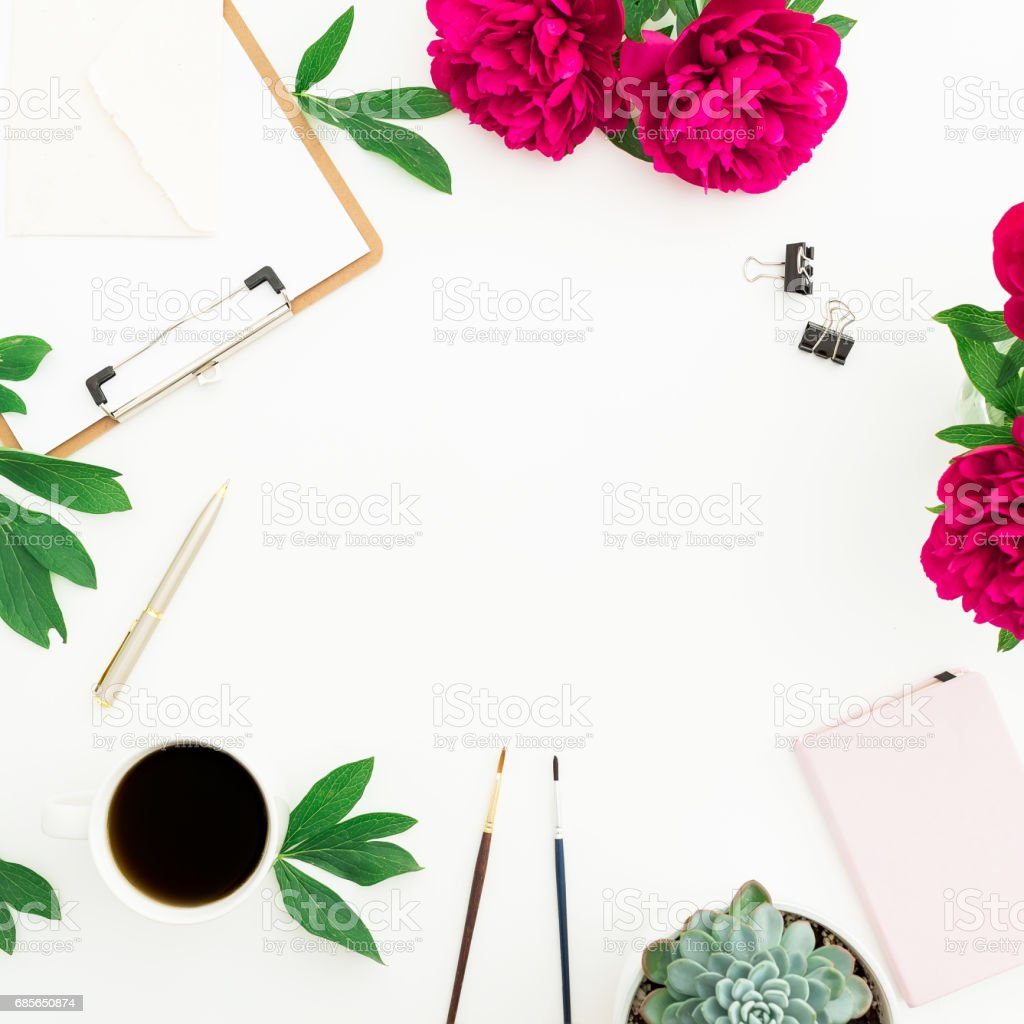 Blogger or freelancer workspace with coffee mug, clipboard, notebook and peony flowers on white background. Round frame. Flat lay, top view. Beauty blog concept. royalty-free stock photo