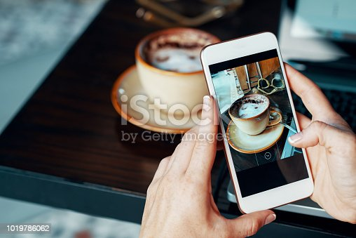 Female blogger taking photo of her coffee to make a post