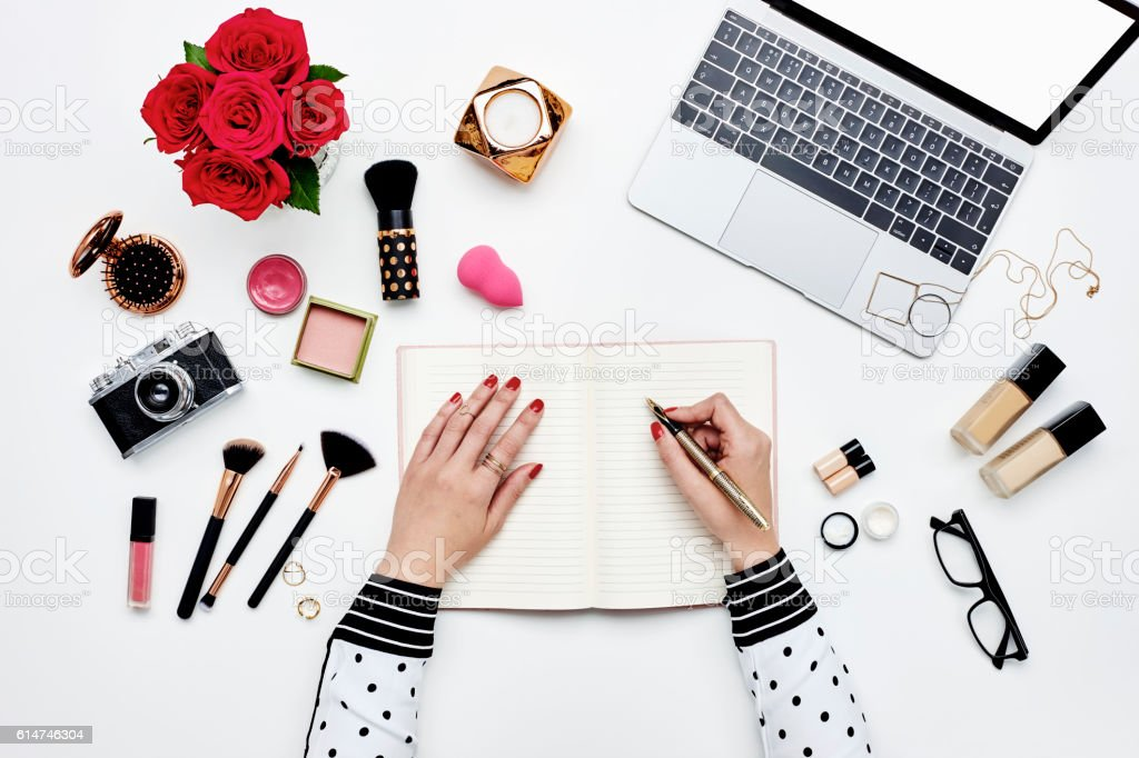 Blogger writing in blank book surrounded with beauty accessories stock photo