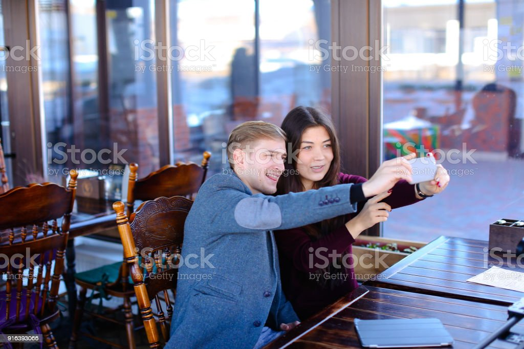 Bloggers take selfie using smartphone in new luncheonette stock photo