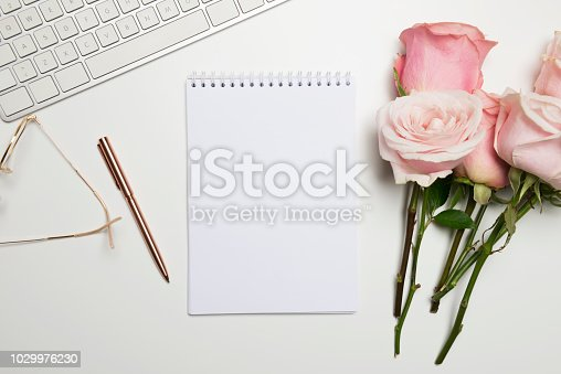Pencil, notepad, keyboard, pen, glasses and roses on white table.