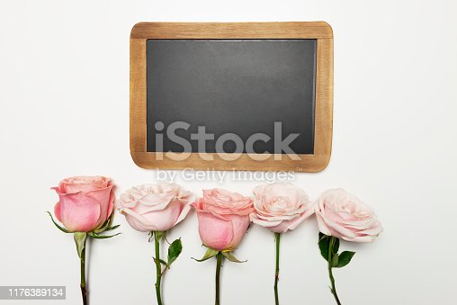 Blackboard 5 pink roses in a row on white table.