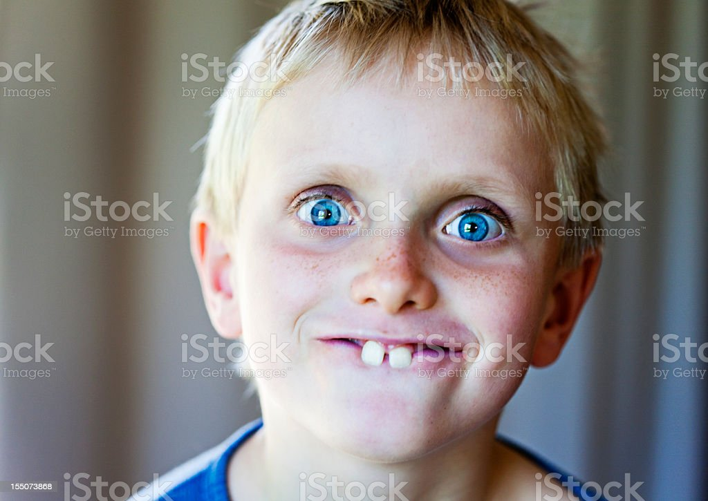 Blond 8 year old boy makes funny Bugs Bunny face stock photo