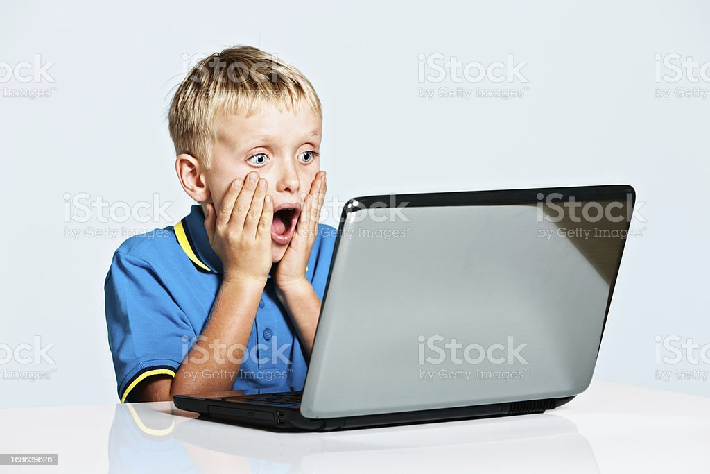 Blond 9 year old boy is shocked by laptop image stock photo