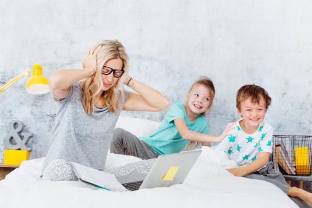 blond und sexy Business-Mama bei der Arbeit, während ihre Kinder im Bett spielen – Foto