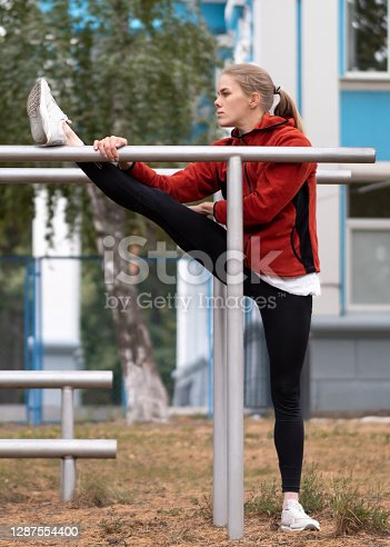 Blond attractive fit Caucasian woman in red hoodie and leggings stretching her legs using parallel bars on the sports area outdoor in summer, vertical photo, selective focus. Motivation, workout, urban fitness, flexibility, gymnastics and good shape concept