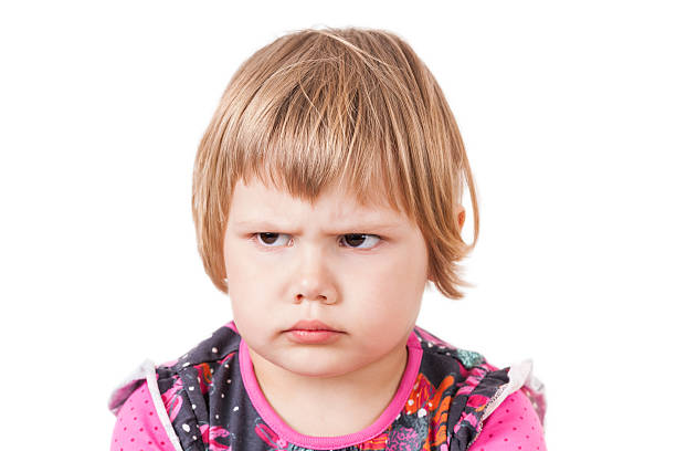 blond baby girl angry frowns, studio portrait - frowning stock photos and pictures