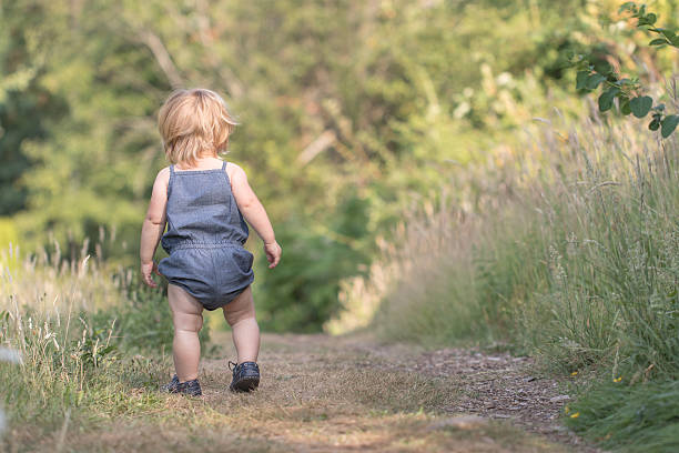 Blond baby walking away down on path stock photo