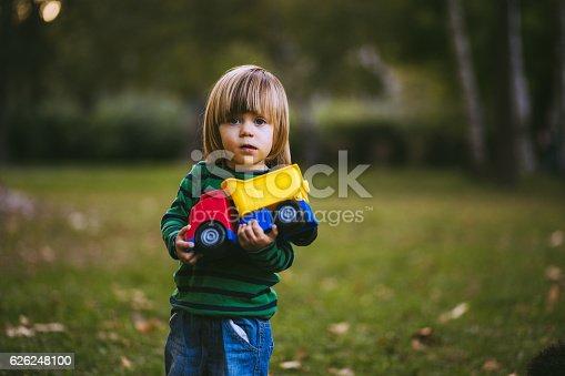 istock Blond Boy Holding Toy Truck in Park 626248100