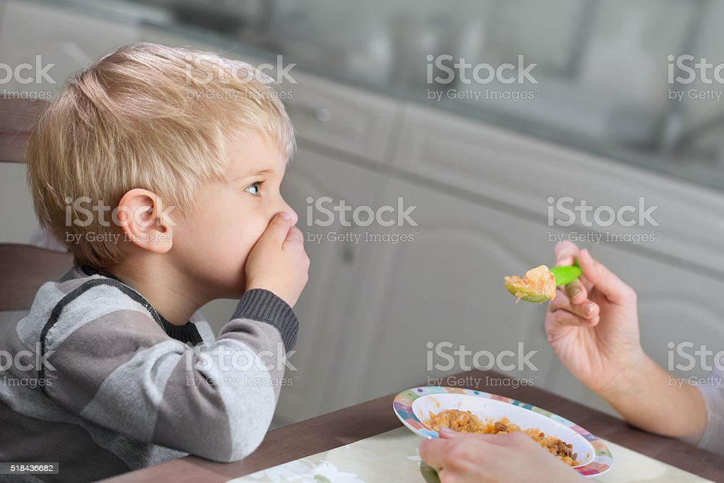 Blond boy holds hand on his mouth to stop eating stock photo