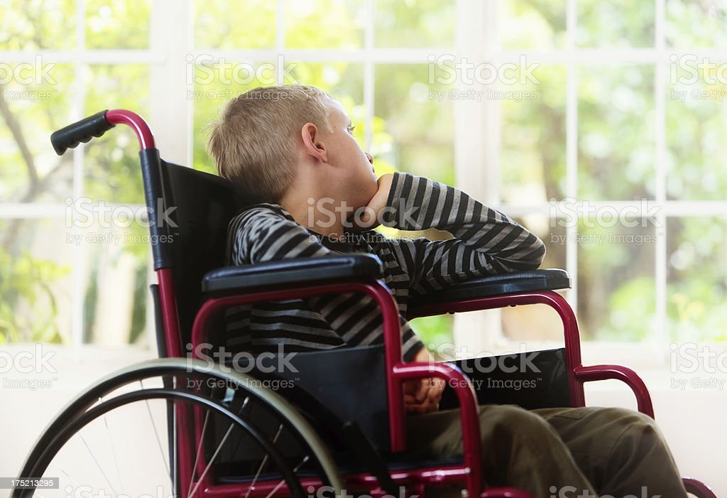 Blond boy in wheelchair looks longingly through window at garden stock photo