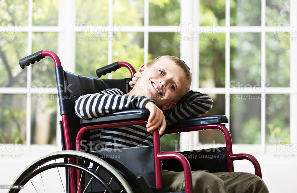 Blond boy in wheelchair seems satisfied with his situation stock photo