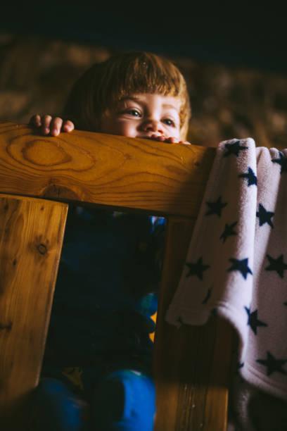 blonder junge sitzt auf bett - etagenbett weiss stock-fotos und bilder