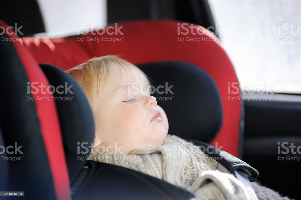 Blond Boy Toddler Sleeping In A Red And Blue Car Seat Royalty Free Stock Photo