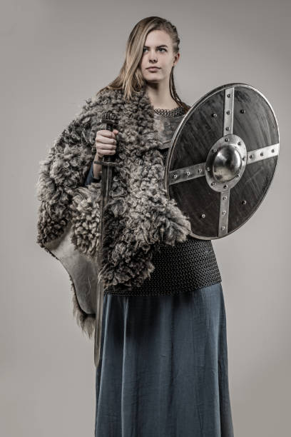 blond braided weapon wielding viking warrior female alone in studio shoot - indumento corazzato foto e immagini stock