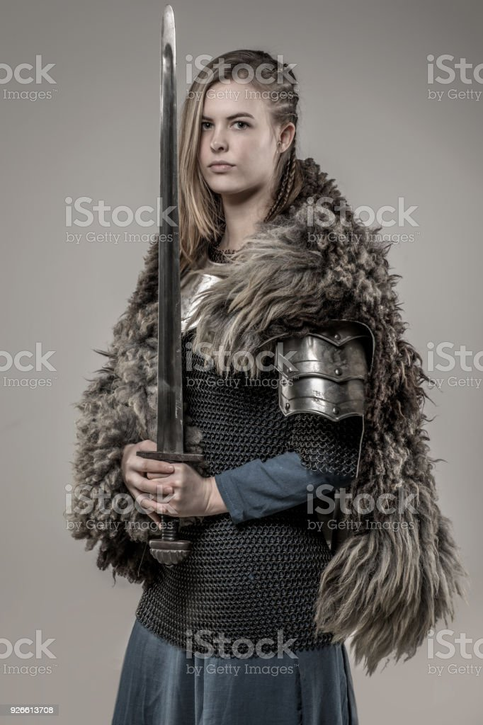 Loira trançado arma empunhando viking warrior fêmea sozinha em fotos de estúdio - foto de acervo