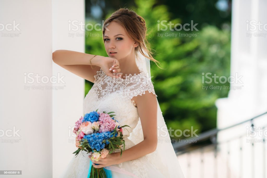 Blond bride with blue eyes posing in wedding dress with bouquet of flowers. The model raised her hand to her face. The wind develops the girl's blonde hair royalty-free stock photo