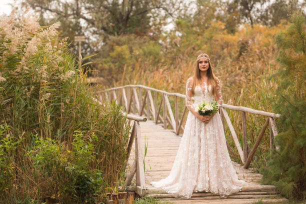 blonde braut mit blumenstrauß posiert vor holzbrücke und langen rasen - brautstrauß aus holz stock-fotos und bilder
