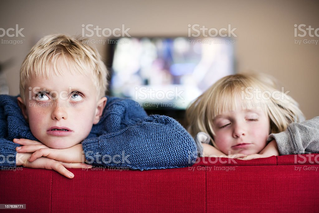 Blond brother & sister sit indoors bored and sleepy stock photo