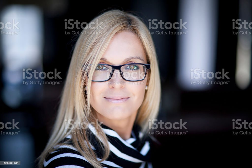 Blond Confident Woman Working At Home. With Glasses. stock photo