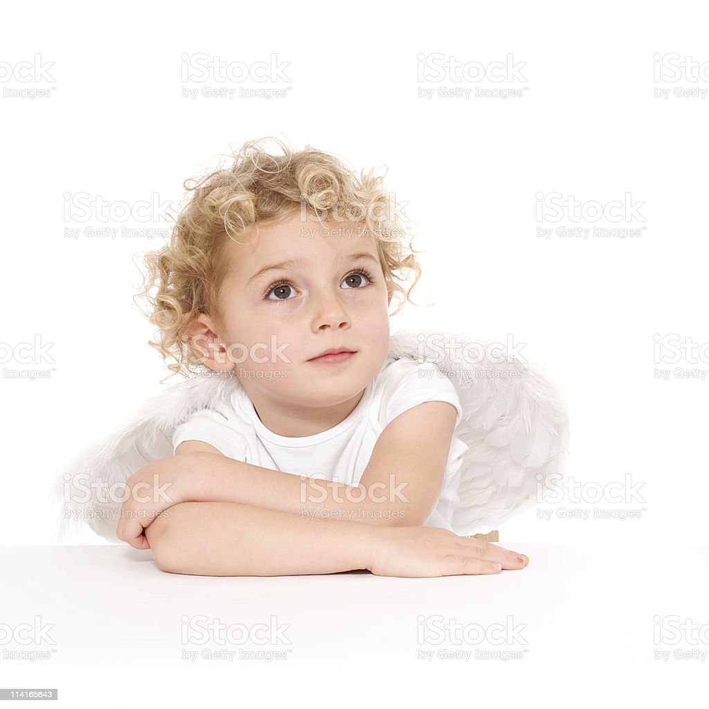 A blond, curly headed child posing as cherub with wings.  royalty-free stock photo