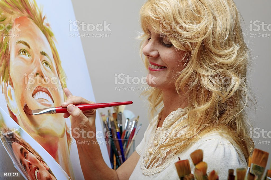 Blond female artist painting a realistic portrait of a man royalty-free stock photo