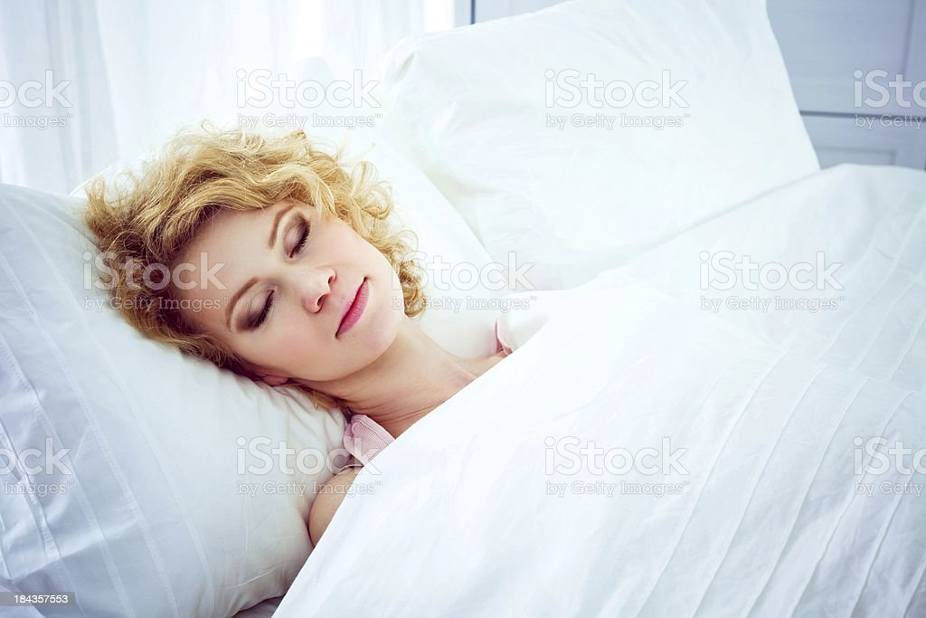 Blond female asleep in bed with white covers Beautifull young adult woman sleeping blissfully in a bed on a white pillow and under white sheet. 20-24 Years Stock Photo