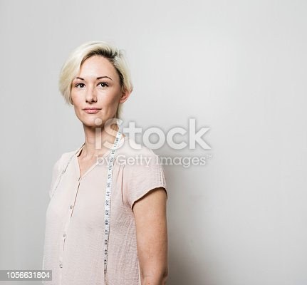 Beautiful mid adult fashion designer looking away. Blond female tailor is standing with tape measure. She is against white background