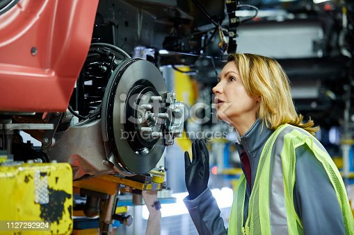 941796726istockphoto Blond female engineer checking vehicle at factory 1127292924
