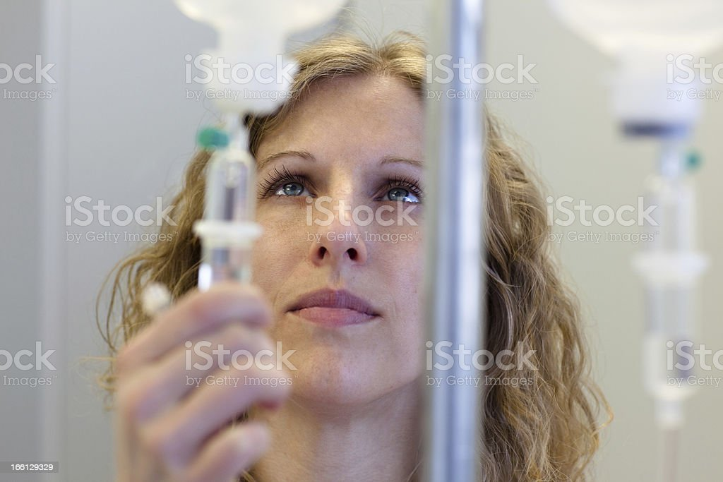 blond female nurse prepares an IV Drip stock photo