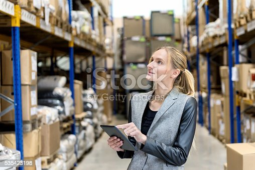 Portrait of a pensive young woman supervisor with digital tablet in hand looking up in warehouse. Young blond woman standing at distribution warehouse and wearing elegant suit. Industrial boss curiously smiling and examining the stock. Logistic worker working in a large distribution warehouse. Large distribution storage in background with racks full of packages, boxes, pallets, crates ready to be delivered. Logistics, freight, shipping, receiving.