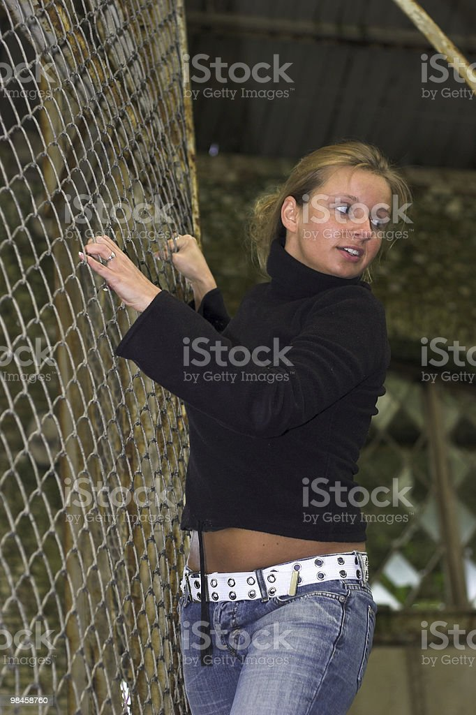 Blond girl climbing a fence royalty-free stock photo