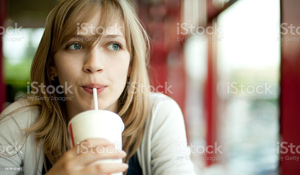 A blond girl drinking a cold beverage while looking outside stock photo