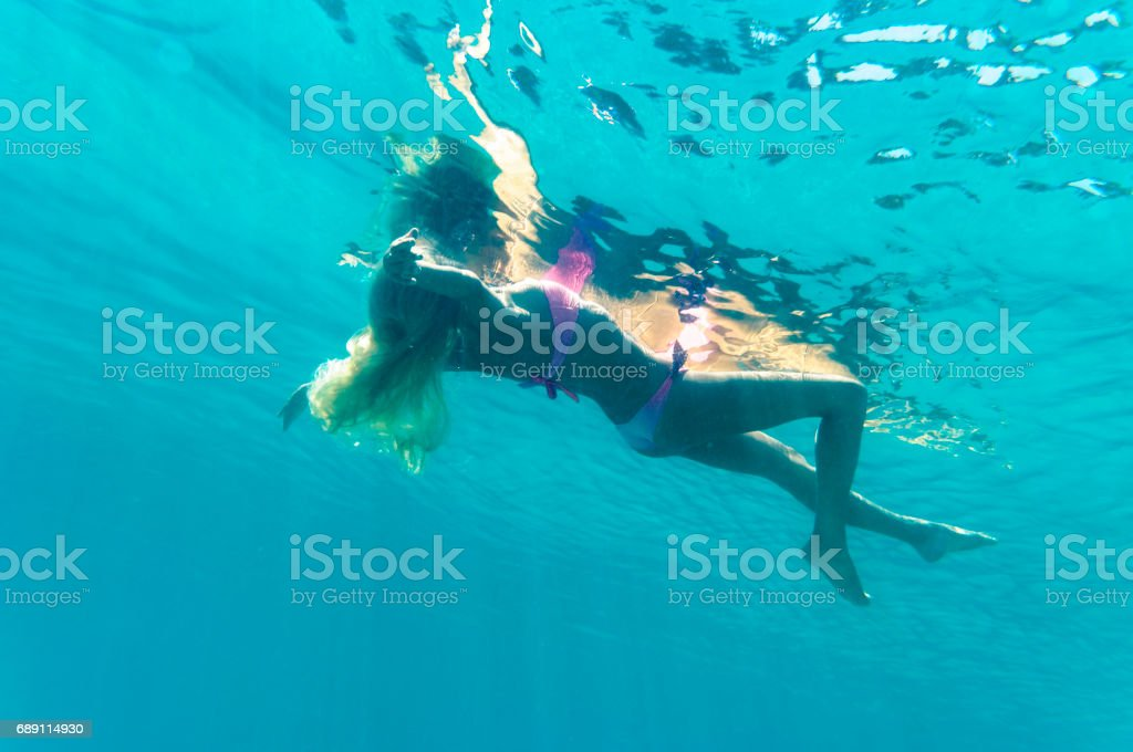 Blond girl floating on water surface stock photo